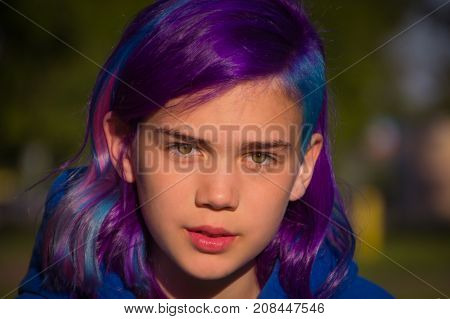 Girl with extreme hair blue, violet, on a green background