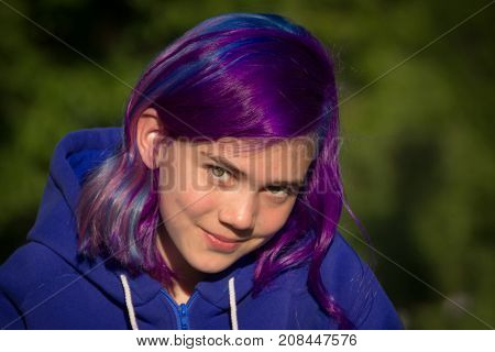 Smiling girl with extreme hair on a green background
