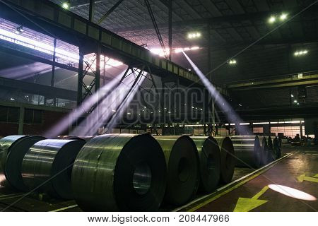 Sun beams bursting through the roof windows of a steel mill shining on steel coils