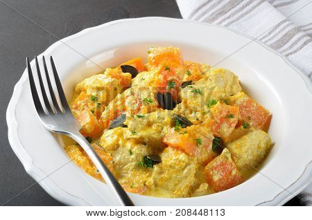 Baked pumpkin with chicken and cream sauce in a white plate on a dark stone background and gray striped napkin closeup