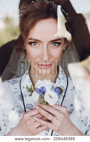Gorgeous Bride In Elegant Robe Holding Boutonniere In Luxury Hotel Room Face Closeup Of Happy Emotio