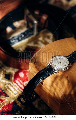 Vintage Black Leather Watch On Wooden Case Near Stylish Belt, Groom's Wedding Attire Concept