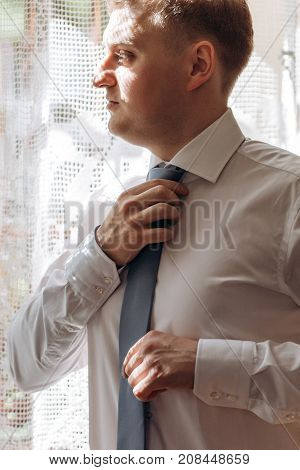 Stylish Groom Putting On Shirt With Cufflinks And Tie At The Window. Elegant Rich Groom  Getting Rea