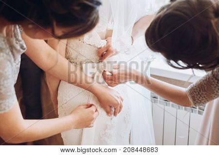 Bride Getting Ready In The Morning. Bridesmaids Helping Bride Put On Lace Wedding Dress, Back View.