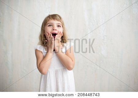 Funny Kid In White Dress Jumping And Laughing On Colored Background. Little Pretty Girl Isolated On