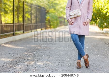 A girl in a pink coat and a white colored purse over her shoulder in a park. Concept - rest. Close-up.