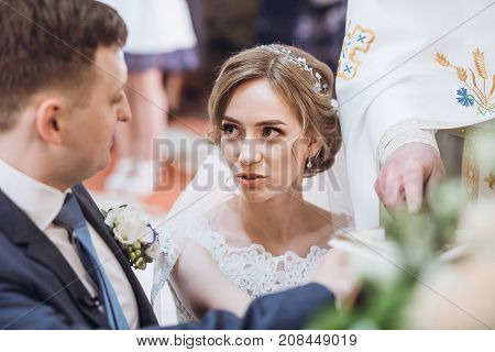 Exchanging Wedding Vows. Bride And Groom Putting Hands On Bible And Saying Wedding Oaths In Church A