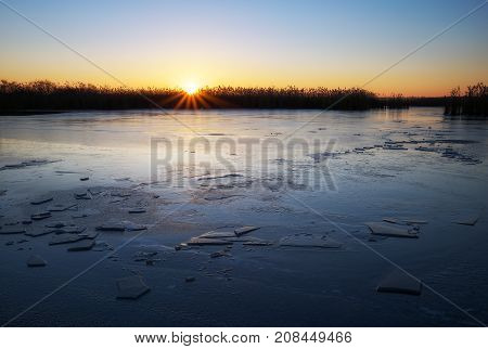 Winter landscape with frozen river reeds and sunset sky. Daybreak