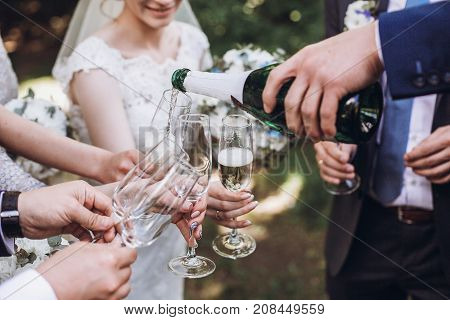 Happy Group Of People Toasting With Champagne. Man Holding Bottle Of Champagne And Pouring Drink Int