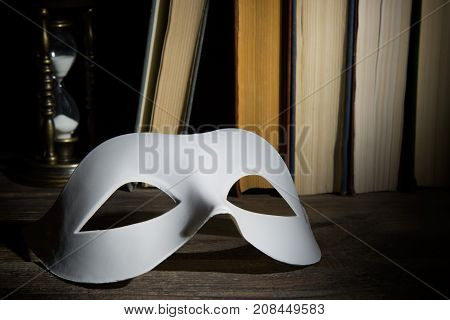 Theater concept. White classical carnival mask on book background with vintage hourglass on wooden table.