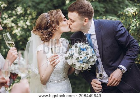 Happy Bride And Groom Kissing And Holding Champagne Glasses. Happy Group Of People Toasting With Cha