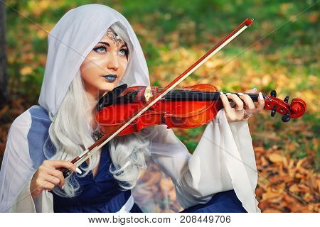 Elf with a violin in the autumn forest. Beautiful Girl In an elf costume playing a musical instrument.
