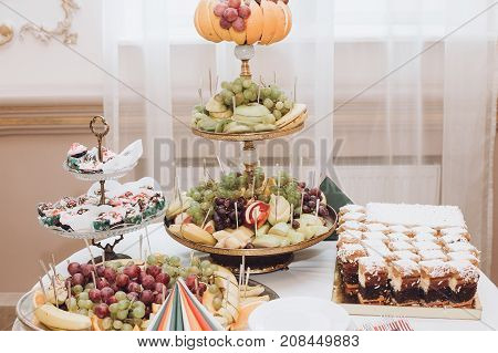 Delicious Fruits On Stand And Desserts Sweet On Table At Wedding Reception In Restaurant. Luxury Cat