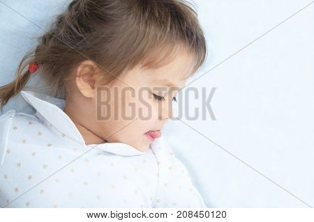 Playful little girl portrait looking down with interest lying on white blanket