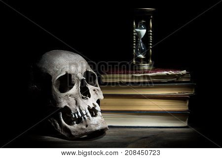 Life is short concept. Skull and vintage hourglass on old book and wooden table.