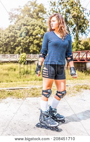 Young woman standing rollerskating or rollerblading outside in summer park with knee and elbow pads looking by bridge