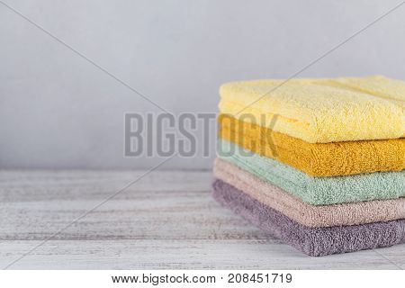 Stack of colorful bath towels on light background. Pastel colors cotton towels. Hygiene fabric spa and textile concept