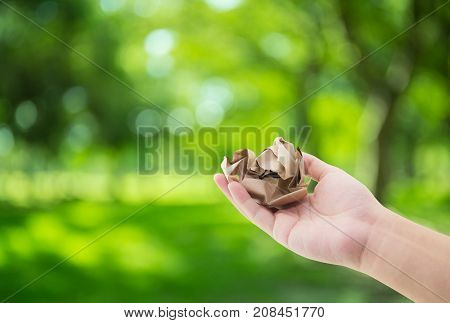 Hand holding crumpled paper on green nature background with environment concept.