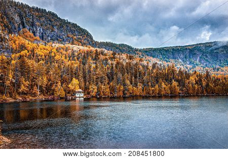 Lake House In Autumn Landscape By Water During Rainy Cloudy Day In Quebec, Canada With Stormy Clouds