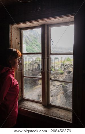 Tourist woman visiting the Helleren houses in Jossingfjord along road 44 between Egersund and Flekkefjord Sokndal municipality Norway.