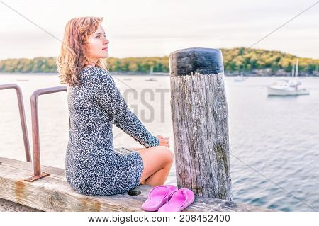 Young Happy Smiling Woman Sitting On Edge Of Dock In Bar Harbor, Maine Looking At Water And Bay With