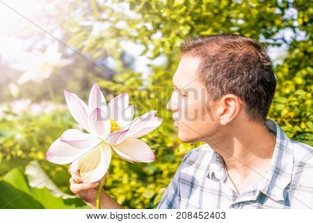 Portrait closeup of young man looking at bright white and pink lotus flower with yellow seedpod inside