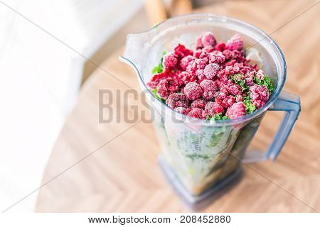 Macro Closeup Of Fresh Green Kale And Frozen Raspberries In Plastic Blender Container For Smoothie