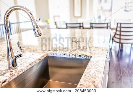 New Modern Faucet And Kitchen Room Sink Closeup With Island And Granite Countertops In Model House,
