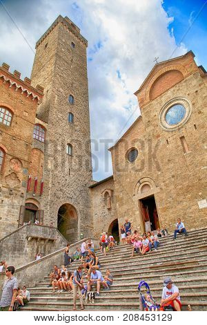 SAN GIMIGNANO, ITALY - JULY 22, 2017 : Tourists in Piazza del Duomo at the medieval town of San Gimignano, Siena, Tuscany, Italy