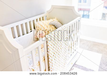 Closeup Of Bright Yellow Baby Crib In Nursery Room With Toys And Pillow In Model Staging Home, Apart