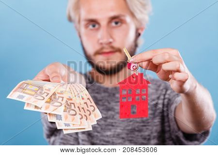 Household savings and finances economy concept. Man holding money and keys with small pendant in the shape of a house studio shot on blue background