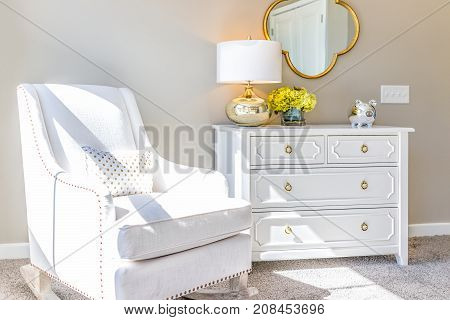 Bright White Modern Rocking Chair In Nursery Room With Chest Of Drawers, Decorations In Model Stagin