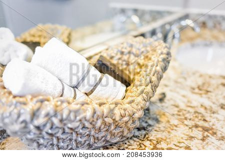 Closeup Of Soap And Hand Towels In Woven Basket In Bathroom Granite Countertop With Sink And Mirror