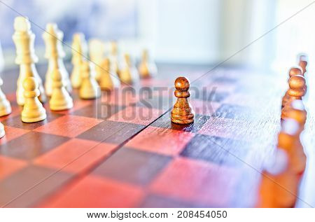 Closeup Of Chessboard With Wooden Pieces On Table In Sunlight And Macro Focus On Pawn