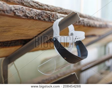 Protective transparent plastic mask from chips hanging on a wooden plank background