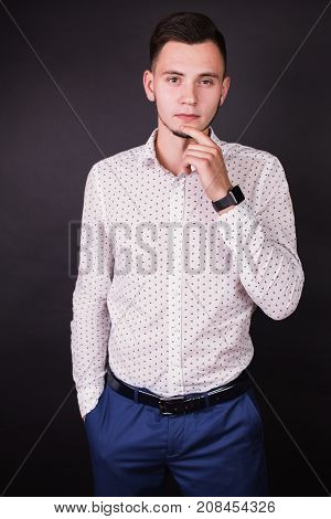 Successful cheerful young businessman in white shirt and black fashionable clock. Stylish cheerful man. A cheerful guy on a black background. A cheerful businessman in a shirt
