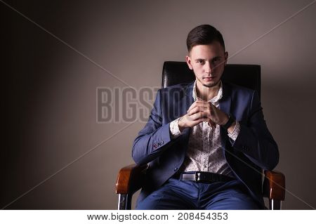 A successful young boss with a confident look in a business suit and white shirt sits on a black leather chair. Stylish boss in chair. Director of the firm in chair. Confident boss in chair