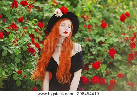 Redhead woman with very long hair in black dress against roses garden. Attractive girl with pale skin with black hat and red veil in green garden. Art photo in summer garden. Girl in red roses garden
