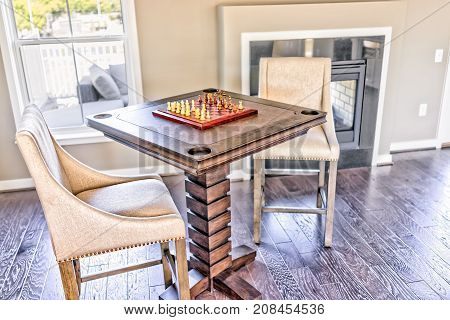 Closeup Of Chessboard Table With Wooden Pieces In Sunlight On Loft Of House With Fireplace And Chair