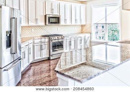 Modern Gray, Brown Kitchen Features Front Cabinets With Granite Countertops And Tile Backsplash With