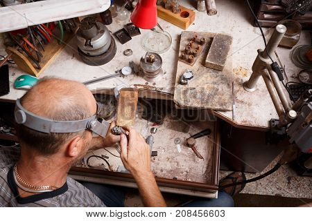 Close-up of a mature jewelry craftsmen making accessory on a messy workshop background. Unique jewelry making equipment and tools.