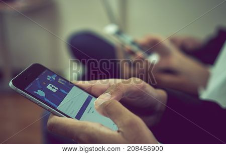 Bangkok Thailand - October 24, 2017 : hand is pressing the Facebook screen on apple iphone6 Social media are using for information sharing and networking.