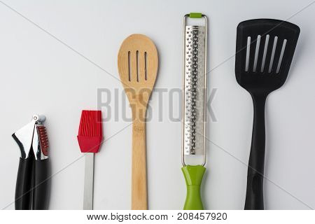 Garlic Press Brush Spoon Spatula Zester on White Background Cropped