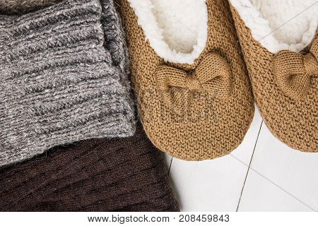 Handmade Warm Knitted Socks From Rough Wool Yarn Fluffy Fir Slippers on White Plank Wood Background. Winter Autumn Eco Fashion Kinfolk Style. Natural Materials.