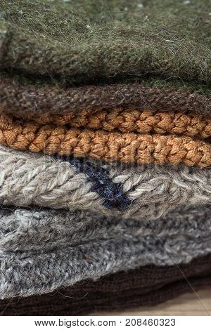 Stack of Handmade Warm Knitted Socks Scarfs Mittens From Rough Wool Yarn Brown Beige Grey. Close up. Winter Autumn Eco Fashion Kinfolk Style. Natural Materials