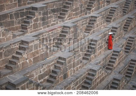 Baswa India : 19th February 2015 - A shot of an Indian female going down lots of stairs at Chand Baori Step Well in India just to get some water.