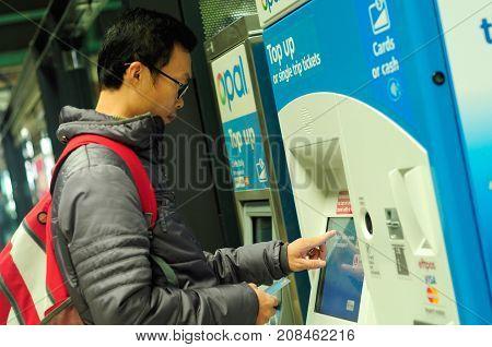 SYDNEY AUSTRALIA -AUGUST 14 2017: Passenger buying train ticket using vending machine at Central railway station Sydney Australia.