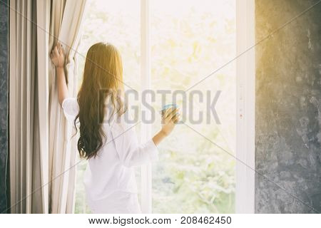 Asian Women Drinking Coffee And Wake Up In Her Bed Fully Rested And Open The Curtains In The Morning