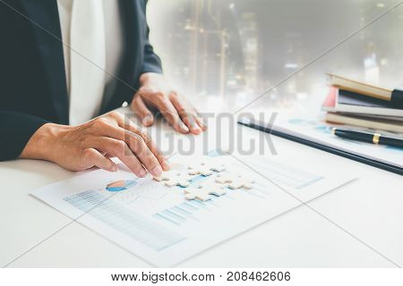Business woman hands connecting jigsaw puzzle. Business solutions success and strategy concept. Close up photo with selective focus.