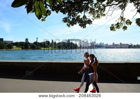 SYDNEY - AUGUST 11 2017:Australian woman runs near the Opera House. Approximately 35% of the Australian population participated at least in one physical recreation activity.